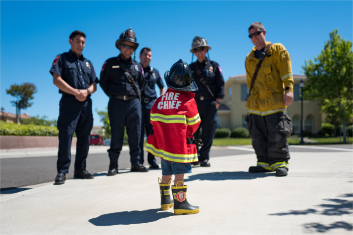 Toddler in Fire Chief outfit gazing up at fire fighters